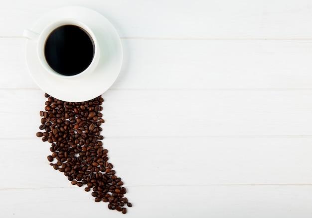 Vista superior de uma xícara de café e grãos de café espalhados em fundo branco, com espaço de cópia
