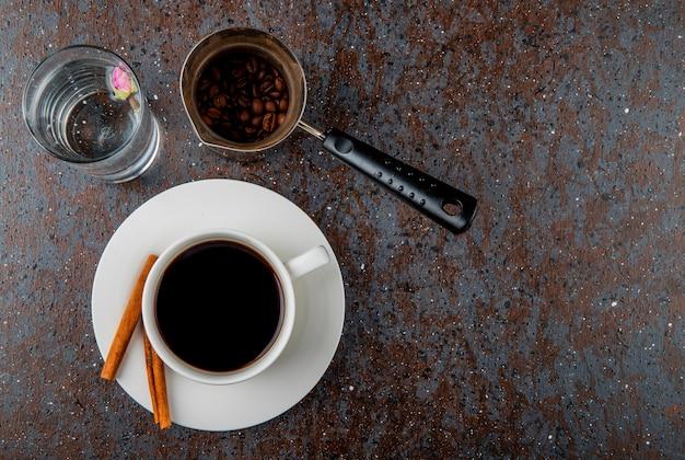 Vista superior de uma xícara de café e uma cafeteira com feijão em fundo preto, com espaço de cópia