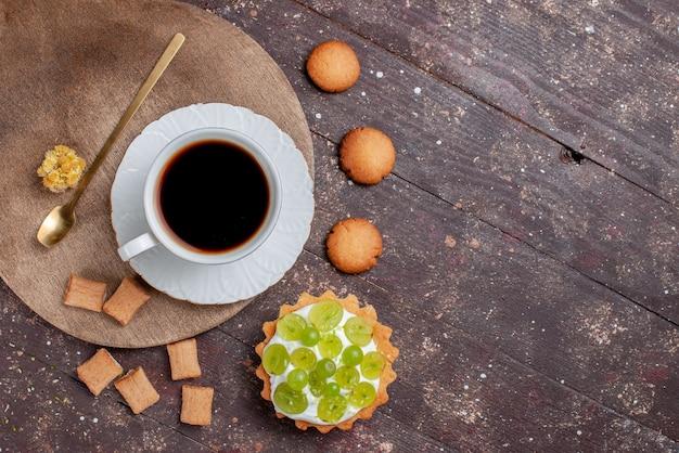 Vista superior de uma xícara de café forte e quente junto com biscoitos e bolo de uva na mesa de madeira, biscoito de café com bolo de frutas
