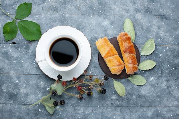 Vista superior de uma xícara de café junto com doces deliciosas bagas de pulseiras em madeira cinza, doce de bolo assado