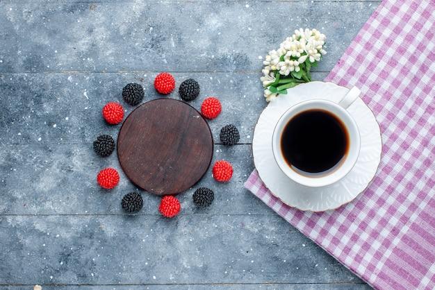 Vista superior de uma xícara de café junto com frutas confiture em um bolo de açúcar cinza e doce