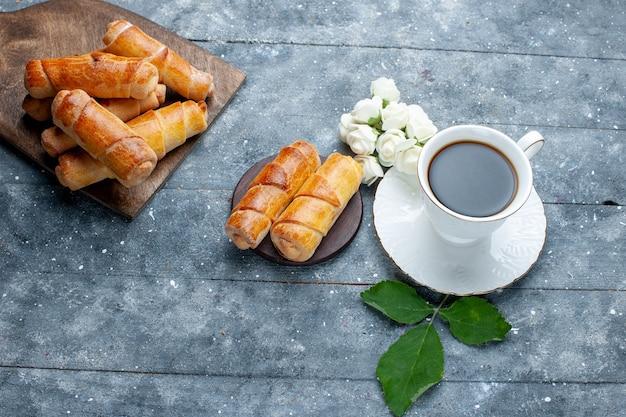 Vista superior de uma xícara de café junto com pulseiras deliciosas e doces em um bolo de massa doce cinza