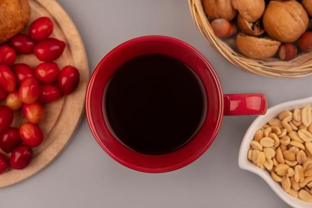 Vista superior de uma xícara de café vermelha com cerejas da cornalina em uma placa de cozinha de madeira com nozes em um balde em uma parede cinza
