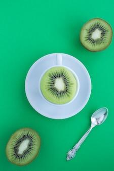 Vista superior de uma xícara de chá branco com kiwi fresco cortado ao meio no fundo verde