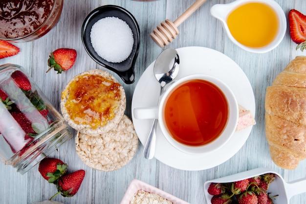 Vista superior de uma xícara de chá com bolos de arroz mel morangos frescos açúcar e geléia no rústico