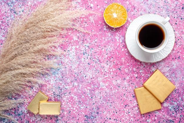 Vista superior de uma xícara de chá com bombons de chocolate na superfície rosa