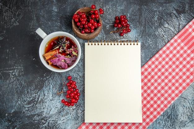 Vista superior de uma xícara de chá com cranberries vermelhas na superfície escura Foto gratuita