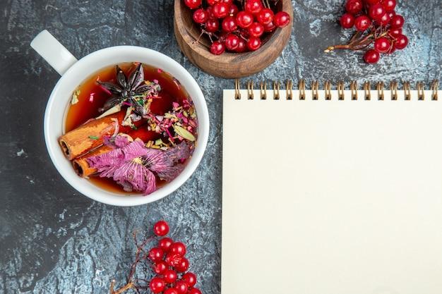 Vista superior de uma xícara de chá com cranberries vermelhas na superfície escura