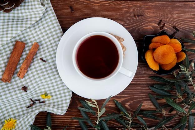 Vista superior de uma xícara de chá com damascos secos e paus de canela na madeira
