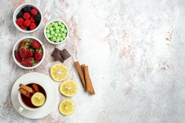 Vista superior de uma xícara de chá com doces e morangos na superfície branca