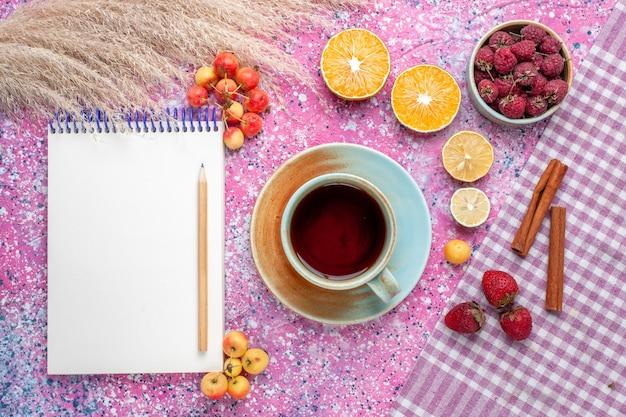Vista superior de uma xícara de chá com fatias de laranja e framboesas na superfície rosa