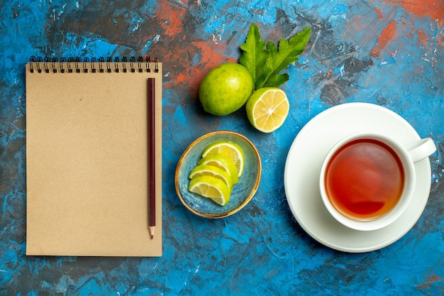 Vista superior de uma xícara de chá com fatias de limão, um lápis no caderno na superfície azul vermelha