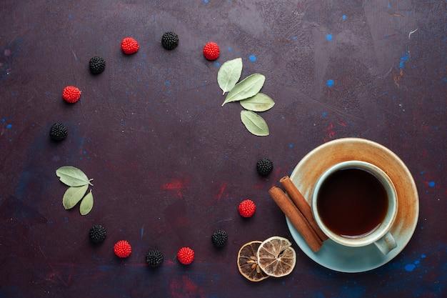 Vista superior de uma xícara de chá com frutas vermelhas na superfície escura