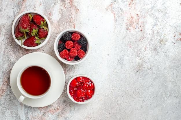 Vista superior de uma xícara de chá com geléia de morangos e confitures na superfície branca