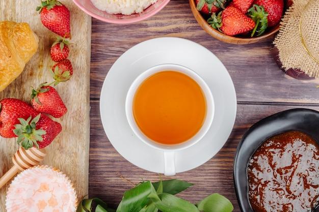 Vista superior de uma xícara de chá com geléia de morangos maduros frescos e queijo cottage na madeira rústica