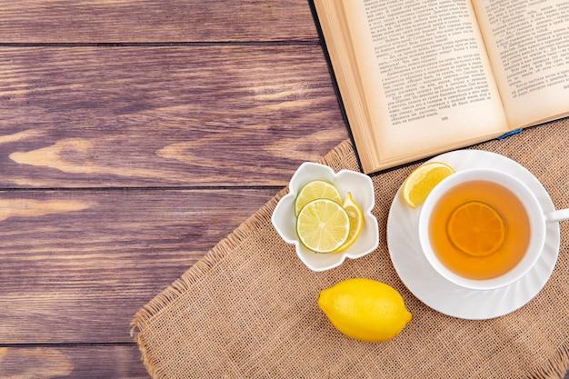 Vista superior de uma xícara de chá com limões frescos em uma tigela branca em um pano de saco em madeira com espaço de cópia