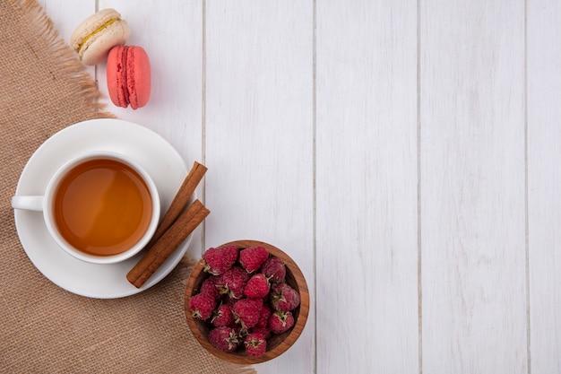 Vista superior de uma xícara de chá com macarons de canela e framboesas em uma superfície branca