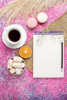 Vista superior de uma xícara de chá com macarons e marshmallow na superfície rosa