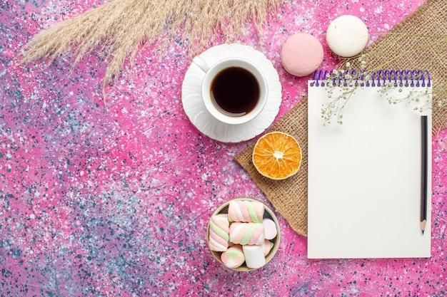 Vista superior de uma xícara de chá com macarons na superfície rosa
