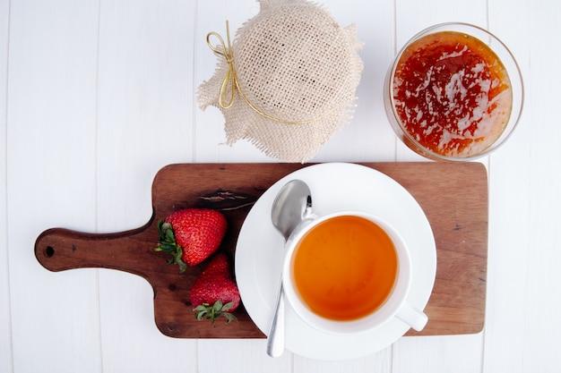 Vista superior de uma xícara de chá com morangos frescos na placa de madeira e geléia de morango em um vaso de vidro na mesa branca