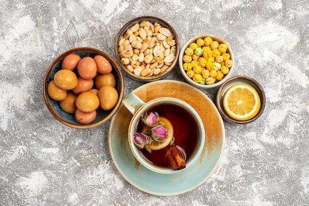 Vista superior de uma xícara de chá com nozes e doces em uma superfície branca clara