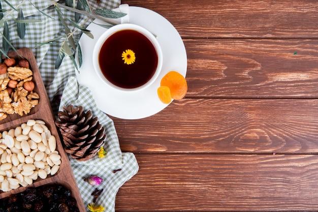 Vista superior de uma xícara de chá com nozes mistas e frutos secos em madeira com espaço de cópia