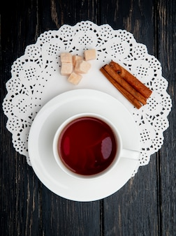 Vista superior de uma xícara de chá com paus de canela e cubos de açúcar mascavo no guardanapo de papel de renda no fundo escuro de madeira