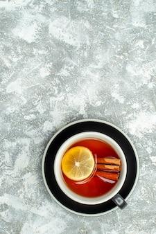 Vista superior de uma xícara de chá com rodelas de limão e canela na superfície cinza do espaço livre