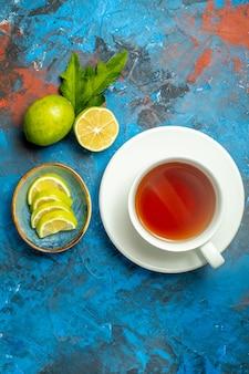 Vista superior de uma xícara de chá com rodelas de limão na superfície azul vermelha