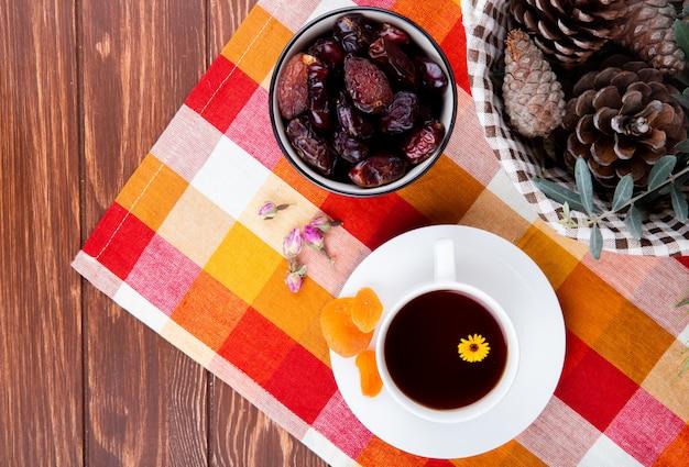 Vista superior de uma xícara de chá com tâmaras secas doces e damascos na toalha de mesa xadrez