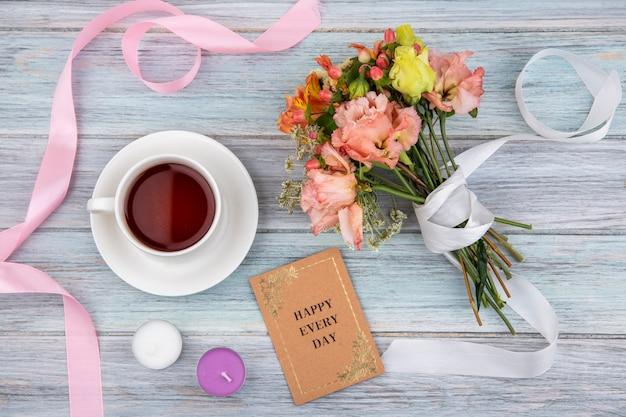 Vista superior de uma xícara de chá com um maravilhoso buquê de flores coloridas amarradas com uma fita branca em madeira cinza