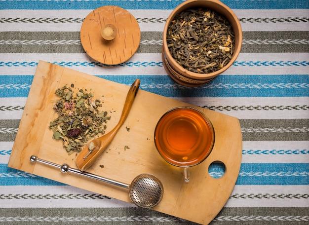 Vista superior de uma xícara de chá com um monte de ervas secas em uma mesa de madeira