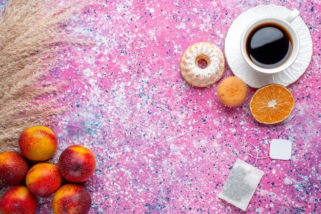 Vista superior de uma xícara de chá com um pequeno bolo e pêssegos frescos na superfície rosa