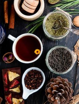 Vista superior de uma xícara de chá com várias especiarias e ervas em potes de vidro no rústico