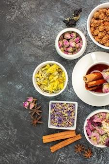 Vista superior de uma xícara de chá de ervas com uma tigela de nozes e diferentes tipos de flores em um fundo cinza