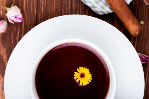 Vista superior de uma xícara de chá decorada com flor dente de leão em madeira