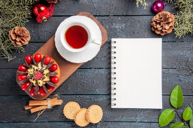 Vista superior de uma xícara de chá e bolo de frutas vermelhas em folhas de brinquedos de natal de pinhas prato de servir de madeira e um caderno na mesa de madeira escura