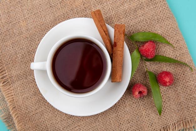 Vista superior de uma xícara de chá e canela no pires com framboesas e folhas no saco