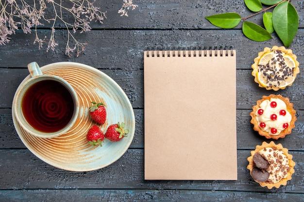 Vista superior de uma xícara de chá e morangos em folhas de tortas de galho de flores secas de disco e um caderno na mesa de madeira escura