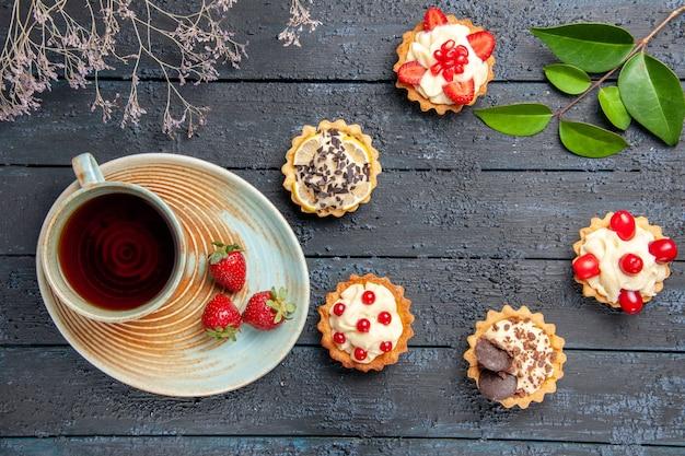 Vista superior de uma xícara de chá e morangos em folhas de tortas de pires na mesa de madeira escura