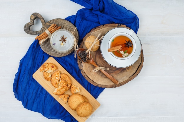 Vista superior de uma xícara de chá na placa de madeira com biscoitos e canela em placas de corte, lenço azul na superfície branca