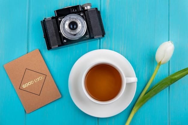 Vista superior de uma xícara de chá no pires e flores com câmera fotográfica e cartão de boa sorte no fundo azul