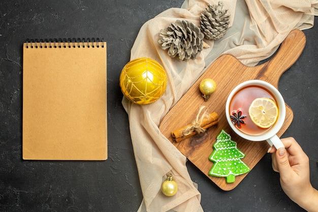 Vista superior de uma xícara de chá preto com limão e lima com canela, acessórios de decoração de ano novo em uma tábua de madeira em um caderno de anúncio de toalha de cor nude