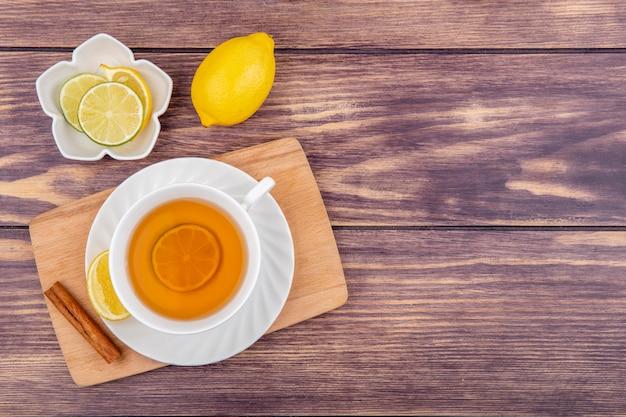 Vista superior de uma xícara de chá preto com limão e pau de canela na mesa de madeira da cozinha com rodelas de limão em uma tigela branca na madeira