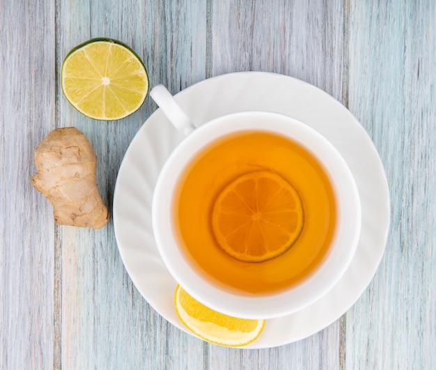 Vista superior de uma xícara de chá preto com rodelas de limão e gengibre em madeira cinza
