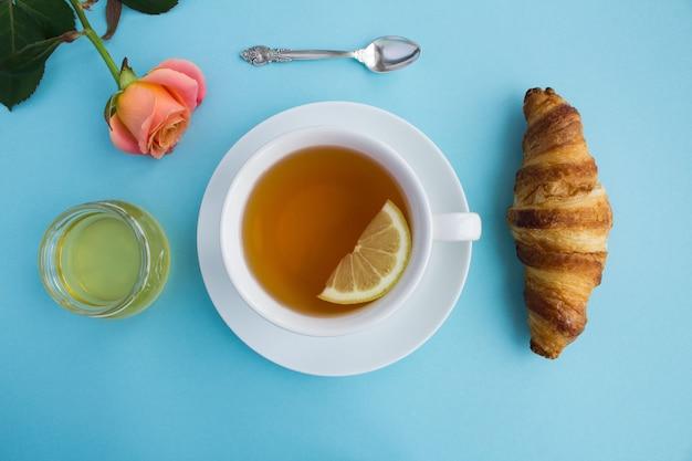 Vista superior de uma xícara de chá preto, croissant, mel e rosa no azul Foto Premium