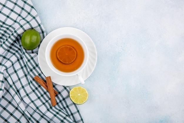 Vista superior de uma xícara de chá preto em uma toalha xadrez em branco com espaço de cópia