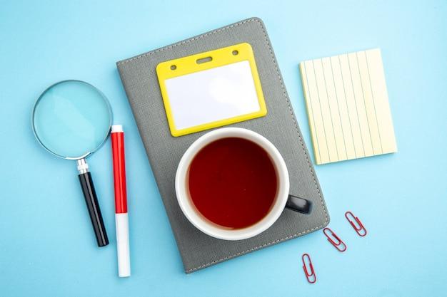 Vista superior de uma xícara de chá preto na caneta de lupa do caderno cinza na superfície azul