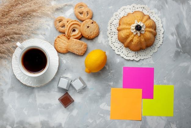 Vista superior de uma xícara de chá quente com bolo de chocolate e limão e biscoitos na luz