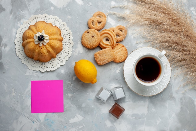 Vista superior de uma xícara de chá quente com chocolate, limão e biscoitos no chão claro.